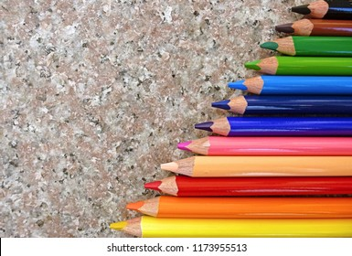 Colored pencils on a beige stone background. Colorful pencils on marble texture. Oblique rainbow row. Versatile use for designs, presentations, illustrations, posters, backgrounds and more