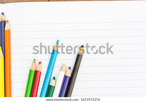 Colored pencils on a blank sheet of paper in a composition notebook