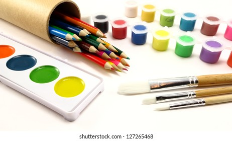 Colored pencils, paint brushes, and paint supplies on a white background
