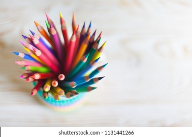Colored pencils in a pencil case on workspace and workshop background