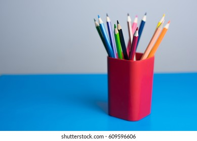 Colored pencils in a pencil case on blue background