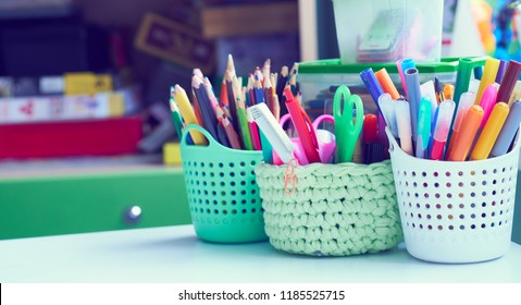Colored pencils, pens, basket with flowers, watercolor paints and other items on wooden desk. Back to school concept.