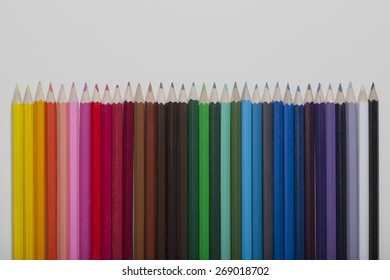 Colored pencils in a row on white backround