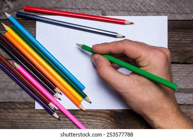 Colored pencils with white paper and pencil in male hand on vintage wooden background