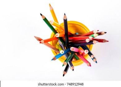 Colored pencils in yellow basket. Multicolored pencils in metal holder, top view.