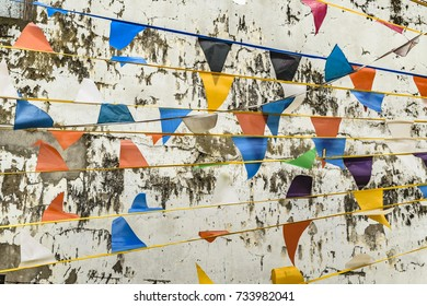 Colored pennants against cracked white wall background
