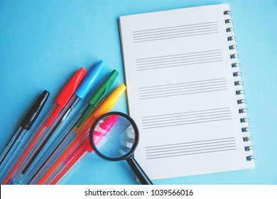 colored pens and magnifier on a white sheet of notepad for text.