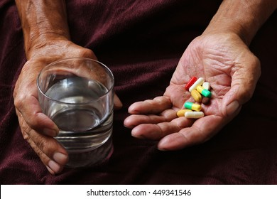 A lot of colored pills and a glass of water in old hands. Painful old age. Health care of older people