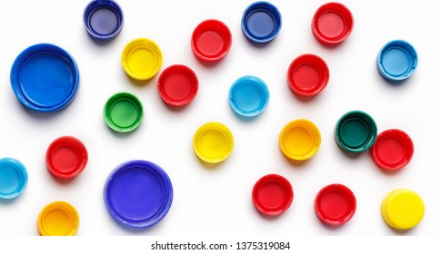 Colored plastic bottle's covers on white background, top view,