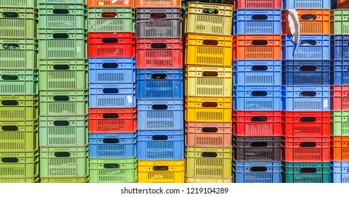 Colored plastic boxes for fruit stacked in piles