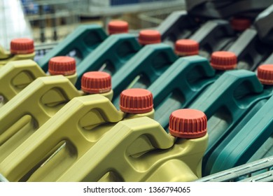Colored plastic cans with engine oil. Rows of canisters placed on a pallet. Limited depth of field.