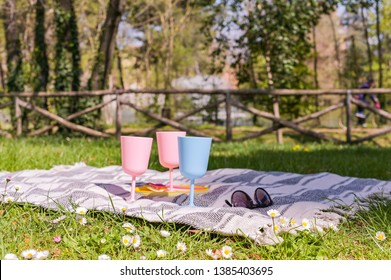Colored plastic picnic utensils. Sunny day in the park and green grass with flowers