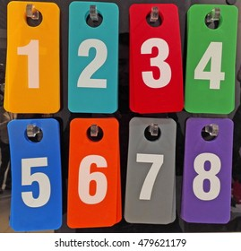 colored plastic plates numbered from one to eight on the hooks in the shopping pavilion large store