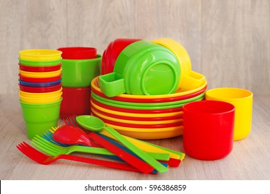 Colored plastic ware. Tableware for a picnic made of colored plastic. A stack of plates, mugs, spoons and forks are included in the set of crockery for picnics, tourism and any travel. Plastic ware.
