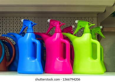 Colored plastic watering spray cans on the shelf