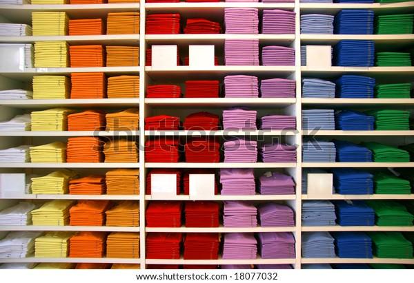 Farbige Polo-Hemden werden in einem Laden ausgestellt. Leere Beschreibungsmarken.
