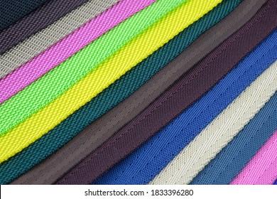 Colored polyester belts, sample palette for making shoulder straps for bags and backpacks. Belt straps for bags, and for sewing dog collars. Colored background from belts folded diagonally.