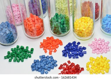 colored polymer resins in test tubes and on white table in lab