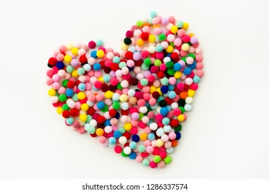 Colored pom poms  in the form of heart on white background. Handmade valenines love decoration. Various colors yarn balls, small cotton balls