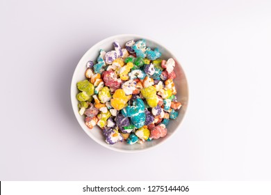 Colored Popcorn candy in white bowl, isolated on white background, soft light, studio shot, copy space. Junk food, fruit flavored popcorn. Colorful, multicolor, candy coated popcorn, top view