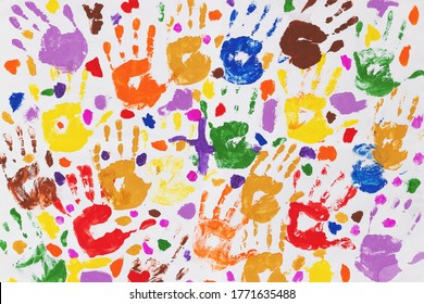 Colored prints of children's hands on a white canvas. A child's handprint on paper. Colored handprints. Many children's multi-colored handprints