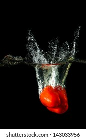 Colored red paprika in water splashes on black background