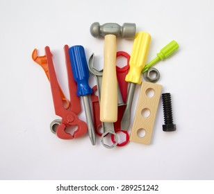 colored set of plastic tools, gathered in a pile on a white background