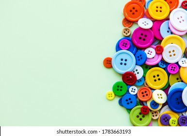 Colored sewing buttons composition on green pastel background. Flat lay with copy space.