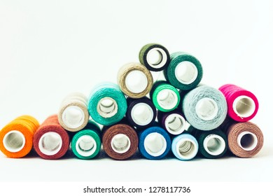 Colored sewing thread coils on white background with copy space for text