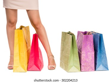Colored shopping bags on the floor. Young woman standing near it over white background. Close-up.