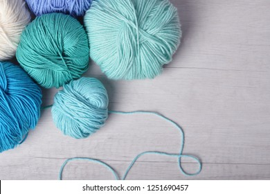 colored skeins of yarn, blue white turquoise concept - colored skeins of yarn on a wooden table preparation for knitting or crocheting