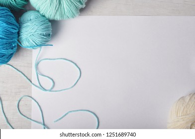 colored skeins of yarn white blue turquoise white paper sheet concept - colored skeins of yarn on a light wooden table with a sheet of white paper preparation for knitting or crocheting