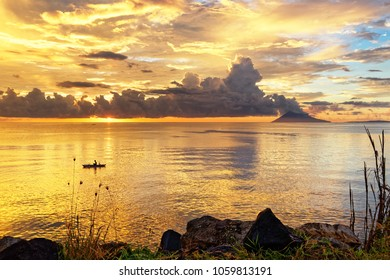 Colored sky at sunset with person in a boat, striking cloud formation and mountain in the background, plants and stones in the foreground - Location: Indonesia, Sulawesi