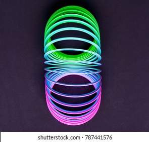 Colored slinky on black mat surface
