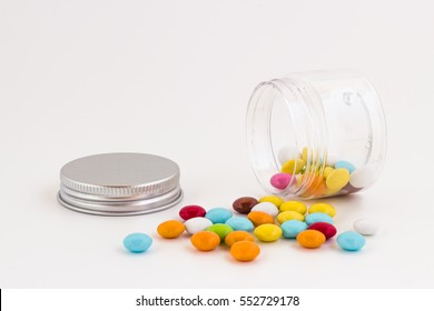 Colored smarties scattered out of an open glass jar, isolated on white background. Shallow depth of field.
