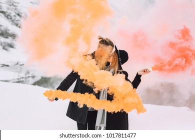 colored smoke held by a very beautiful couple in nature in the winter