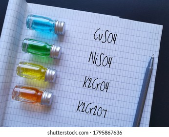 Colored solutions in glass reagent bottles - copper sulfate blue, nickel sulfate green, potassium chromate yellow and potassium dichromate orange. Transition metal compounds with chemical formulas.