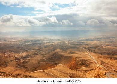 Colored stone desert valley under sun bright cloudy sky.View from a rock (mountain) top. National park HaMakhtesh HaGadol (Large Crater). Unique relief geological erosion land form. Negev,Israel