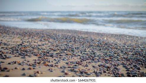 Farbige Steine am Strand, mit Wasserwellen im Hintergrund.