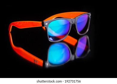 colored sunglasses. on a dark background with reflection