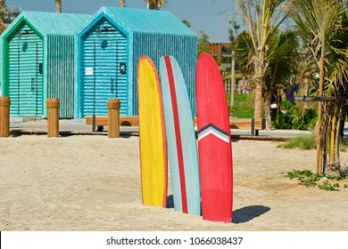 Colored surfboards and beach bathing cabins in Dubai, United Arab Emirates