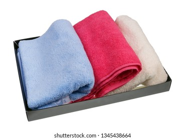 Colored terry new bath towels in a cardboard box. Isolated on white studio closeup