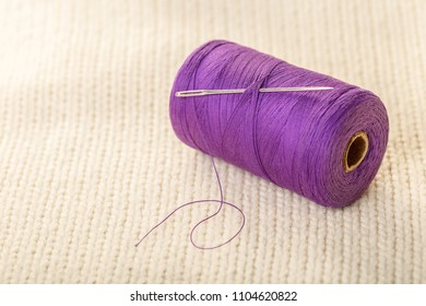 colored thread and buttons on white knitted fabric