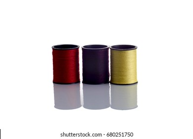 Colored thread coils on white background, sewing, place for text