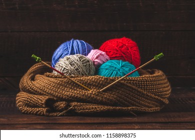 Colored thread for knitting, knitting needles and a knitted, brown scarf on a dark background. Knitting