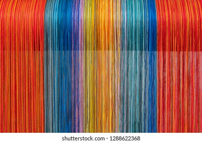 Colored threads of an ancient wooden loom .