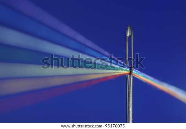 Colored threads passes through a needle's eye - symbolize refraction