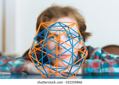 Colored three-dimensional model of geometric solid against the background of the young man's face de-focused. Selective focus on foreground.