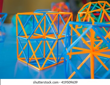 Colored three-dimensional model of geometric  solids on the blue table de-focused.
