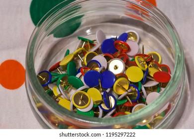 colored thumbtacks in a glass jar, horizontal image